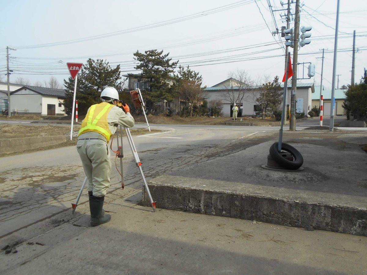写真:道路で測量をしている